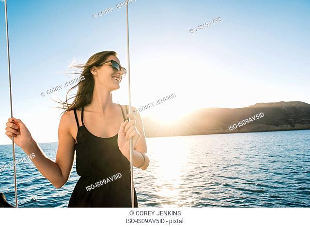 Woman enjoying view on sailboat, San Diego Bay, California, USA