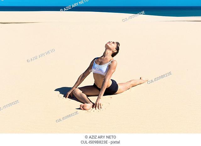 Woman on beach head back in yoga position