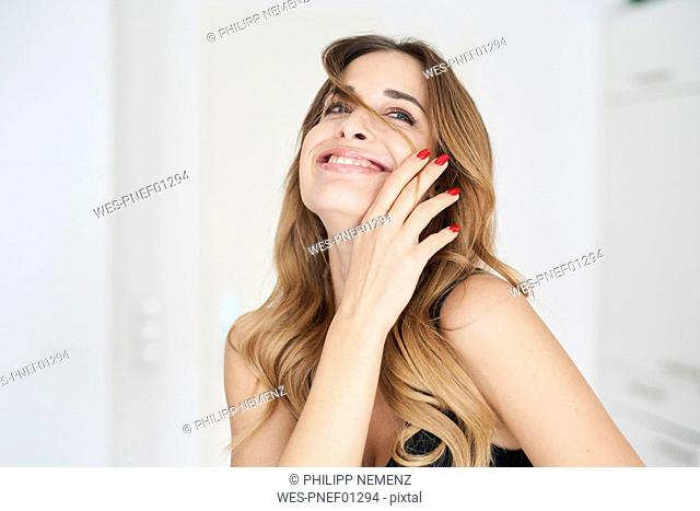 Happy young woman playing with her hair