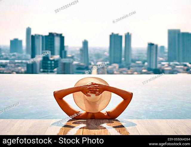 Back view of young woman in hat relaxing in swimming pool on the roof top of hotel and enjoy cityscape. Summer vacation, luxury concept