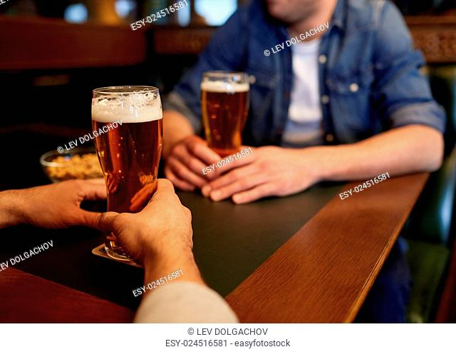 people, men, leisure, friendship and communication concept - close up of male friends drinking draft beer at bar or pub