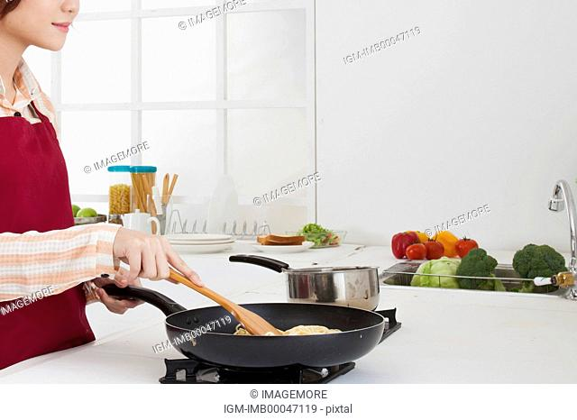 Young woman cooking in the kitchen with smile