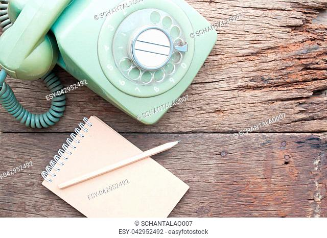 Vintage style home phone with notebook diary on grunge wooden table
