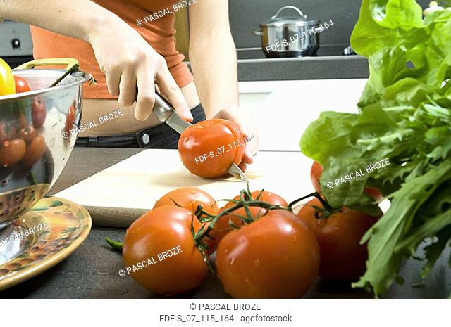 Mid section view of a woman cutting a tomato with a kitchen knife