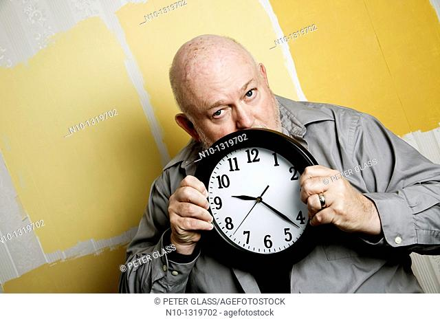 Middle-age balding man holding a clock