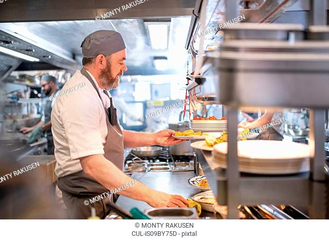 Chef preparing dishes in Italian restaurant kitchen