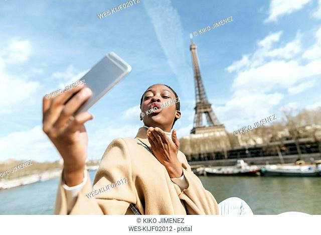 France, Paris, Woman taking a selfie with the Eiffel tower in the background