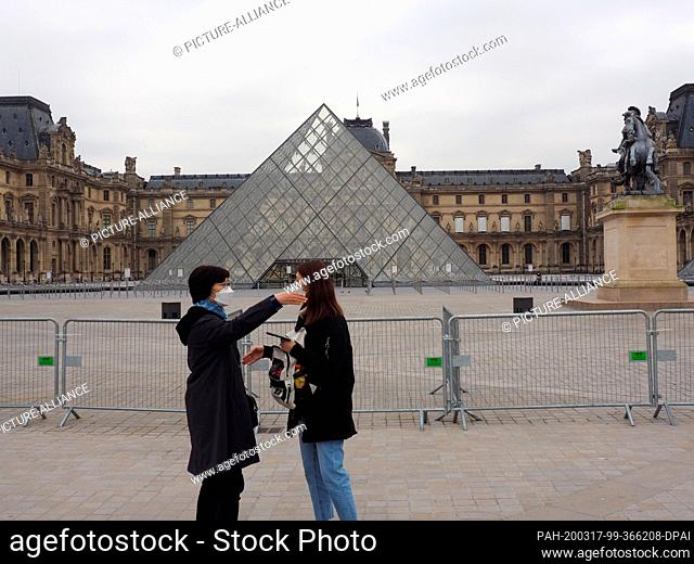 17 March 2020, France, Paris: Tourists wearing breathing masks stand in front of the closed Louvre Museum. By order of the president
