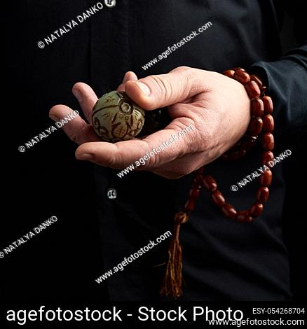 adult man in black clothes holds in his hands a stone magic ball, object for religious rituals, meditations and alternative medicine