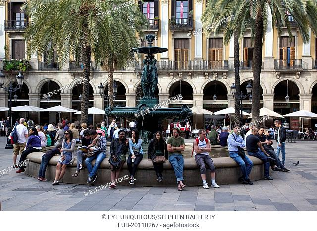 Tourists sat around the fountain in Placa Reial