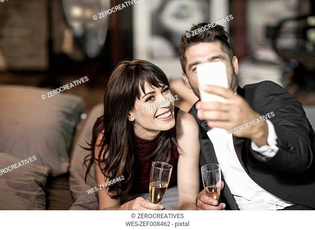 Smiling couple in elegant clothing drinking champagne in bed and taking a selfie