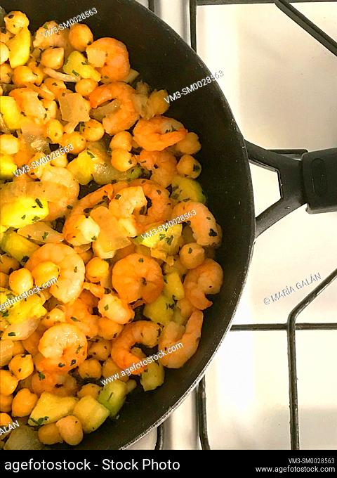 Cooking chickpeas with prawns and courgette