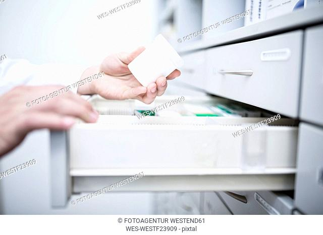 Close-up of pharmacist taking medicine from cabinet in pharmacy