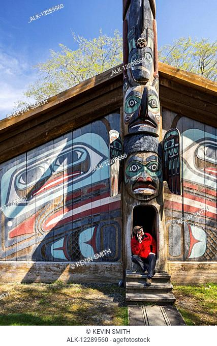 Man sits on steps of a Tlingit clan house with smart phone, Totem Bight Historic State Park, Ketchikan, Southeast Alaska, USA, Spring