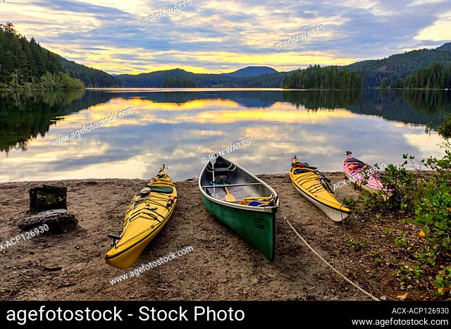 Kayaks and a canoe rest on the shore of Main Lake, in Main Lake Provincial Park on Quadra Island, British Columbia, Canada