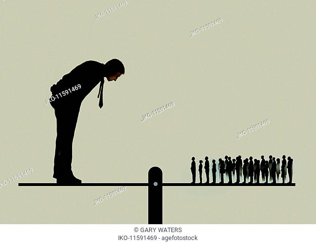 Large businessman looking down on crowd of people on opposite end on seesaw