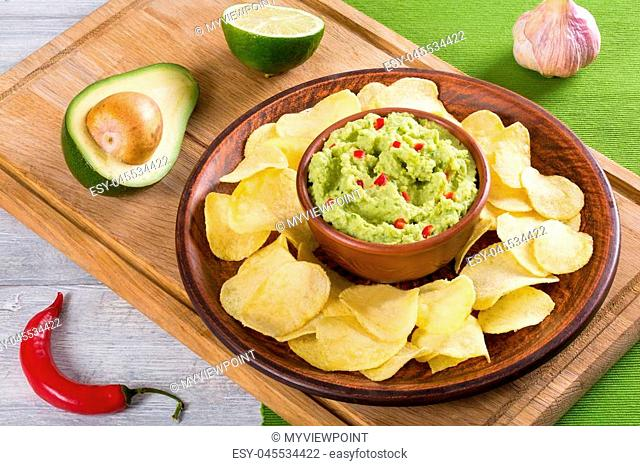 bowl of guacamole dip and potato chips on a clay brown dish, on a green table mat with slice of lime on a white wooden background, view from above