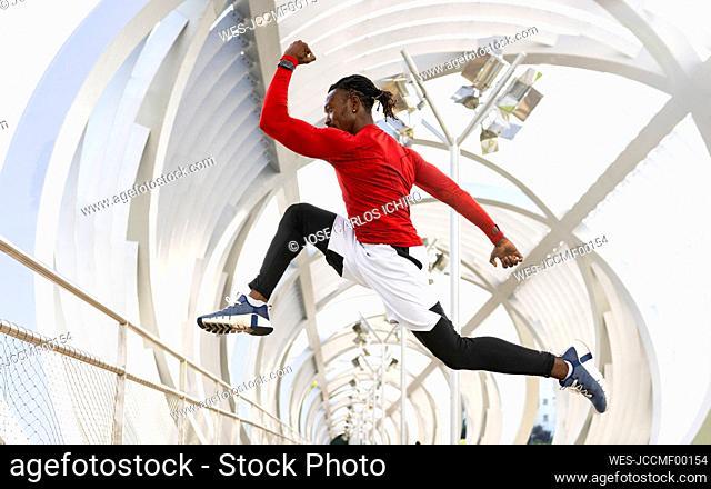 Sportsman exercising while running on walkway
