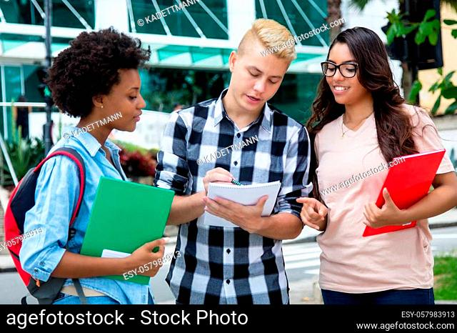 Caucasian male student with african american and latin girls outdoors in the city