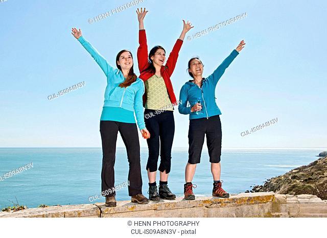 Three female friends waving from wall at coast