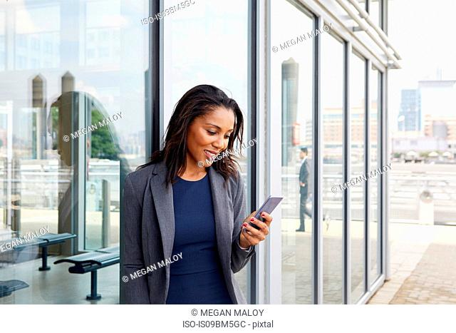 Businesswoman using cellphone outside ferry terminal