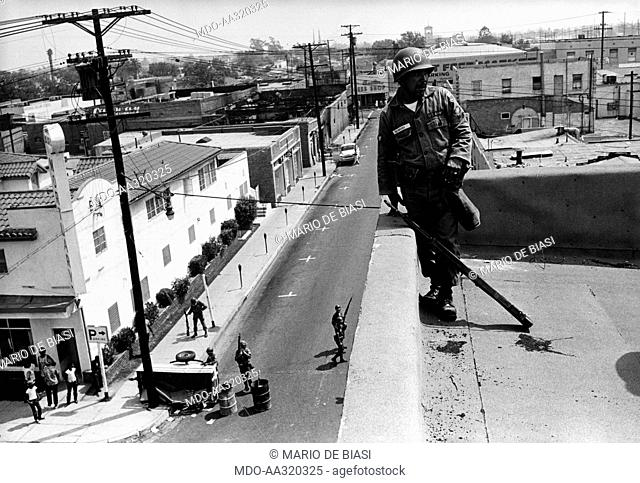 The National Guard patrolling 103rd Street. US National Guard soldiers patrolling the 103rd Street area following race riots. Los Angeles, August 1965