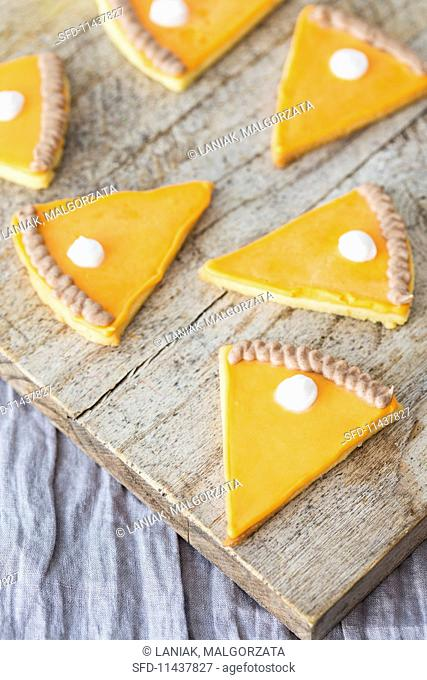 Cookies shaped like slices of pumpkin pie with icing