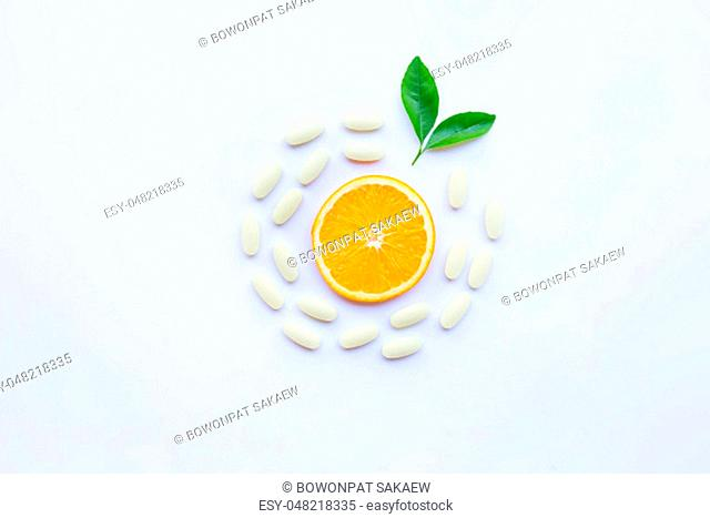 Vitamin C pills with orange fruit and green leaves on white background