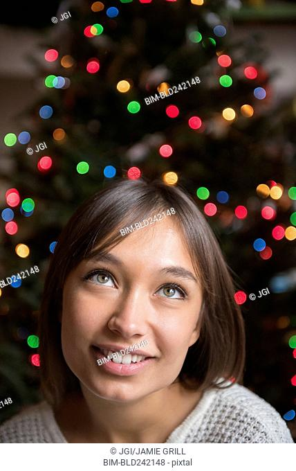 Pensive Mixed Race woman near Christmas tree