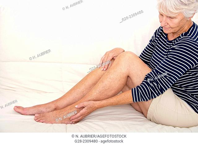 Senior woman sitting on her sofa and holding her painful ankle and legs