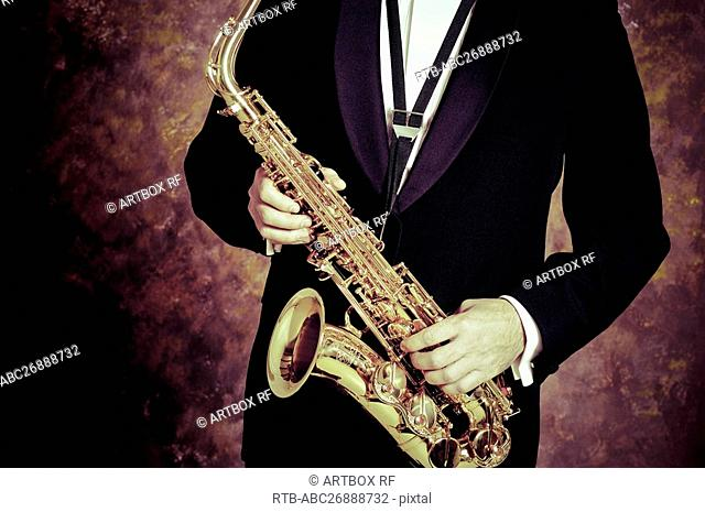 Mid section view of a person playing a saxophone