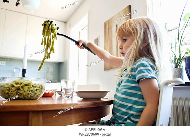 Side view of girl holding tagliatelle pasta in fork over bowl at home