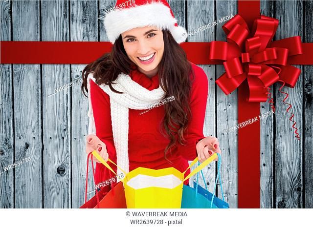 Beautiful woman in santa costume holding shopping bags