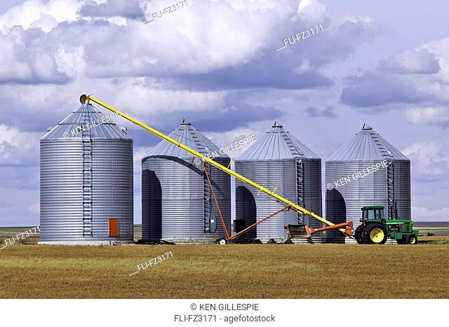 Grain auger and tractor ready to fill silo, Assiniboia, Saskatchewan