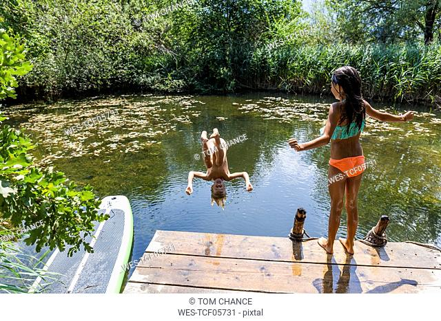 Girl watching her friend jumping into pond