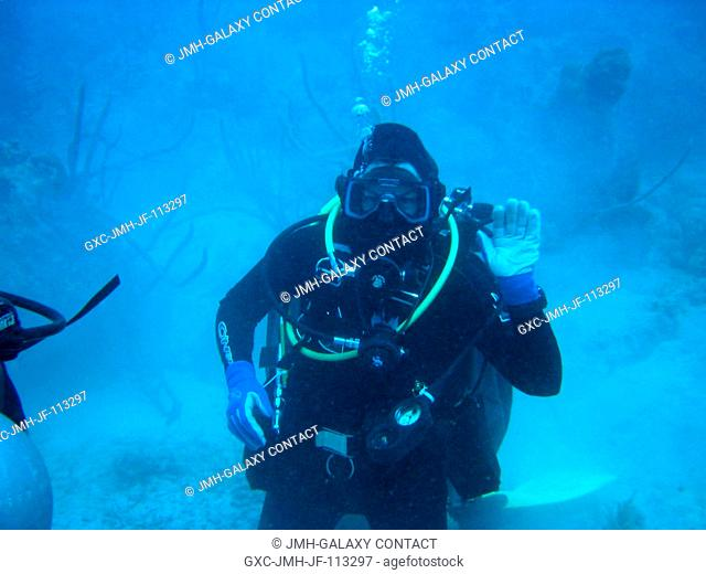 Equipped with SCUBA gear, astronautaquanaut Catherine G. (Cady) Coleman, NEEMO-7 mission specialist, waves from the bottom of the sea during an extravehicular...