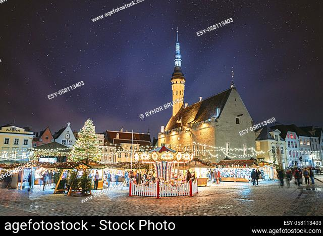 Tallinn, Estonia. Night Stars Sky Above Traditional Christmas Market And Carousel On Town Hall Square. Christmas Tree. Famous Landmark
