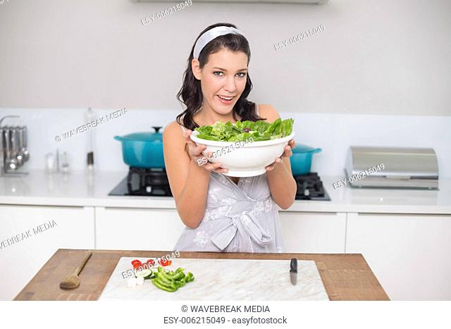 Content pretty brunette holding healthy salad
