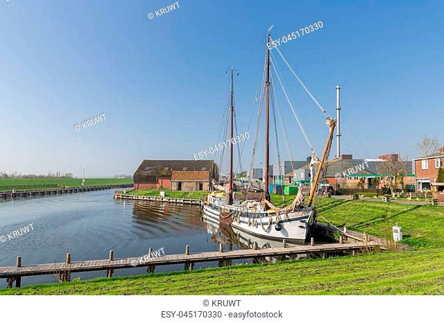 Outer harbor with wooden sailing vessel in old historic Dutch fishing village Workum