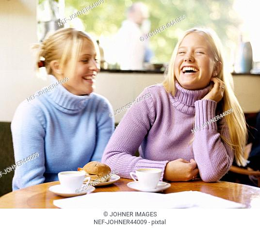Laughing women sitting at the table and have coffee