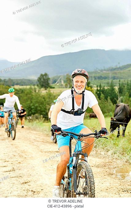 Smiling, confident mature man mountain biking on rural dirt road