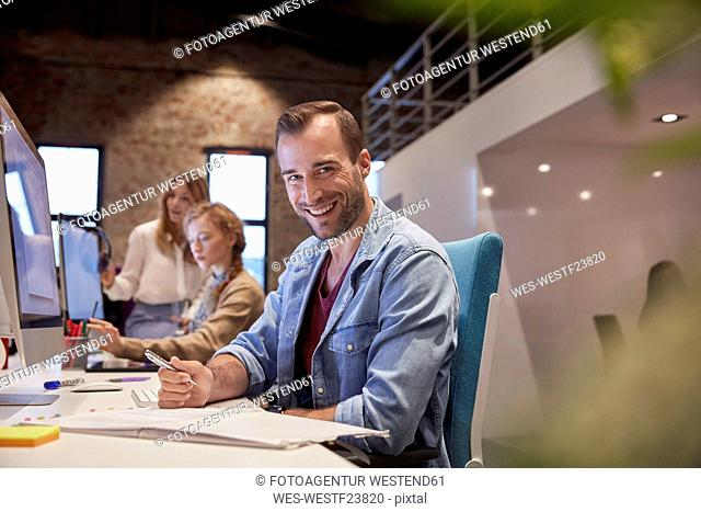 Man working at desk in office, smiling
