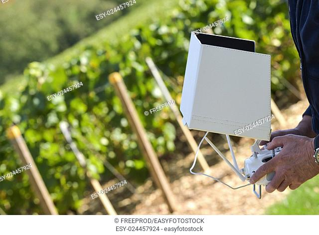 Drone with camera flying against sky in vineyard