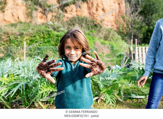 Boy showing his messy hands, full of soil