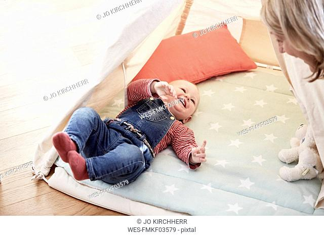 Happy baby girl lying on blanket looking at grandmother