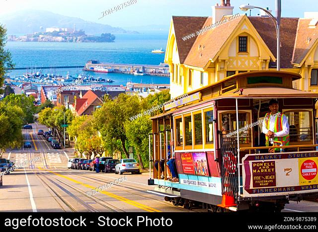 San Francisco, USA - May 10, 2016: Brakeman appying cable car brakes going downhill on steep Hyde Street hill with sweeping view of Alcatraz Prison