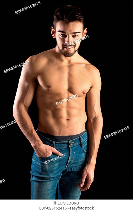 Handsome and muscular young man posing isolated in black