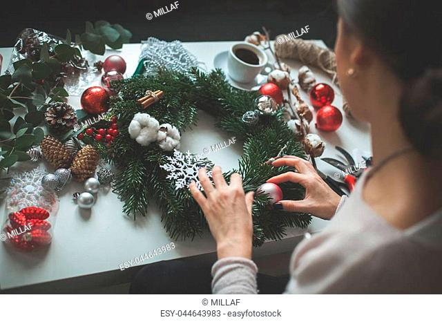 Decorator's Workplace. Woman making Christmas Garland