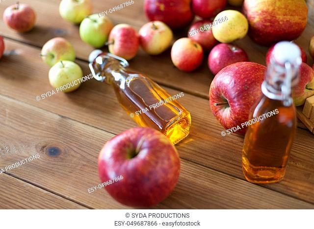 bottles of apple juice or vinegar on wooden table