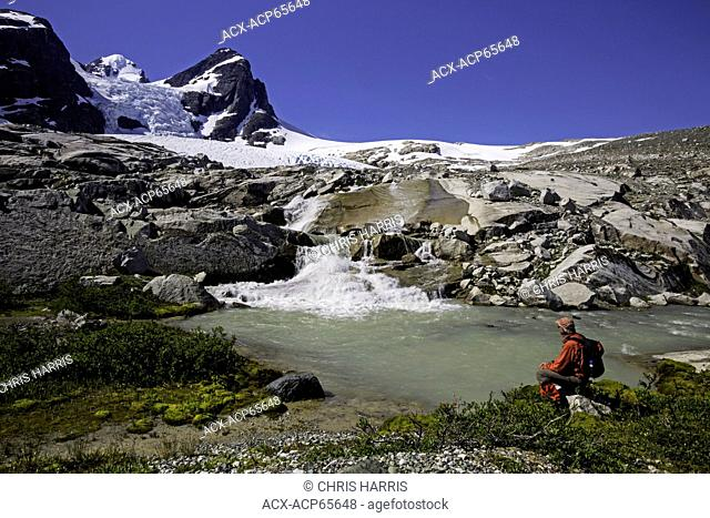 Hiker near stream and glacier, Chilcotin, Coast Mountains, British Columbia, Canada